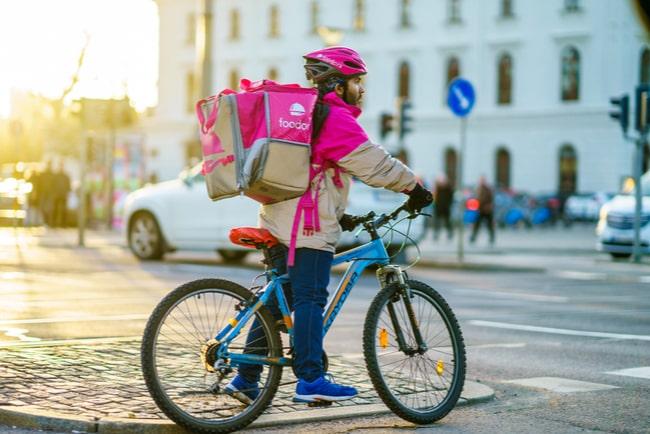 Foodorabud står med sin cykel vid ett trafikljus och väntar på att det ska bli grönt.