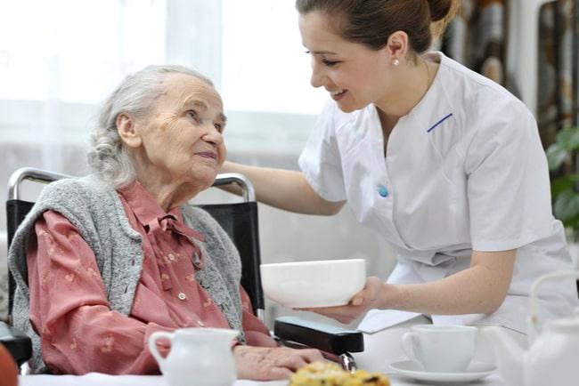 Äldre kvinna på ett äldreboende med en kvinnlig vårdpersonal.