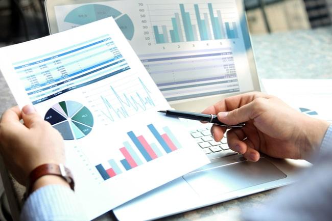 analytiker arbetar med grafer och siffror på papper och dator