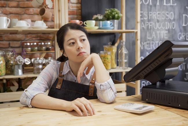 uttråkad kvinna sitter vid disken på kafé utan kunder