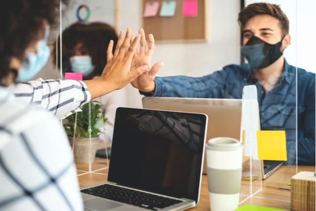 Tre arbetskollegor som sitter på ett kontor med munskydd och en uppsatt glasskiva mellan sig för att minska smittspridningen av Covid-19.