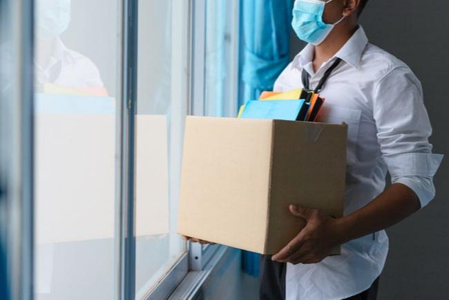 man med munskydd tittar ut genom fönstret och håller i kartong med jobbdokument