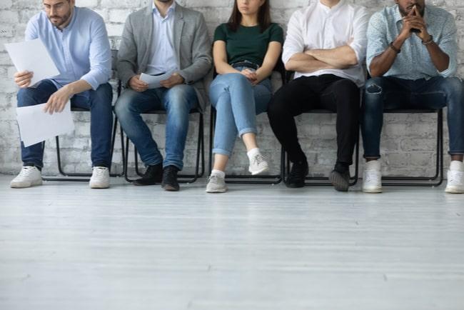 människor sitter i kö i väntan på arbetsintervju