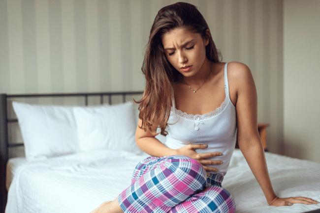 En bild på en kvinna som har ont i magen
