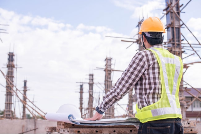 En byggnadsarbetare blickar ut över en byggnadsplats