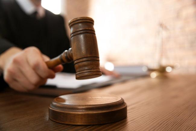hand med domarklubba i rättssal