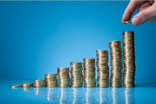 hand placerar mynt på mynthögar