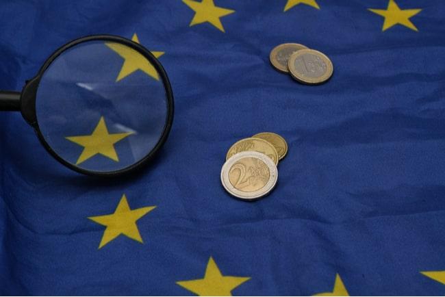 förstoringsglas och mynt på en EU-flagga
