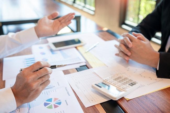 egenföretagare räknar intäkter vid skrivbord med papper och laptop