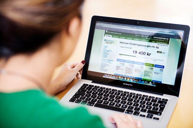kvinna framför laptop med Försäkringskassans hemsida uppe på skärmen