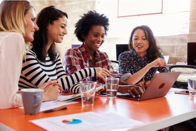 Fyra glada kvinnor sitter vid ett bord och arbetar tillsammans på en laptop.