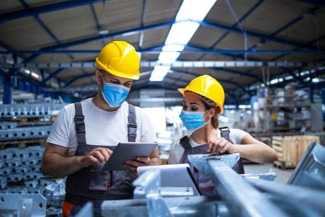 två industriarbetare med bygghjälmar och munskydd diskuterar sitt arbete
