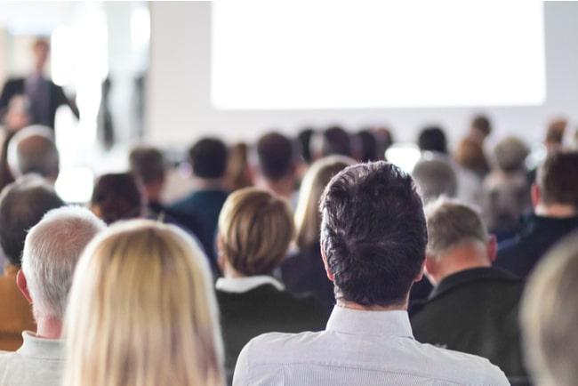 folksamling lyssnar på talare i konferenssal