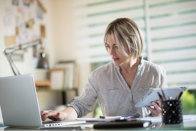 Medelålders kvinna sitter på sin arbetsplats och skriver på sin laptop