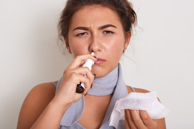 förkyld kvinna med nässpray och näsduk tittar in i kameran