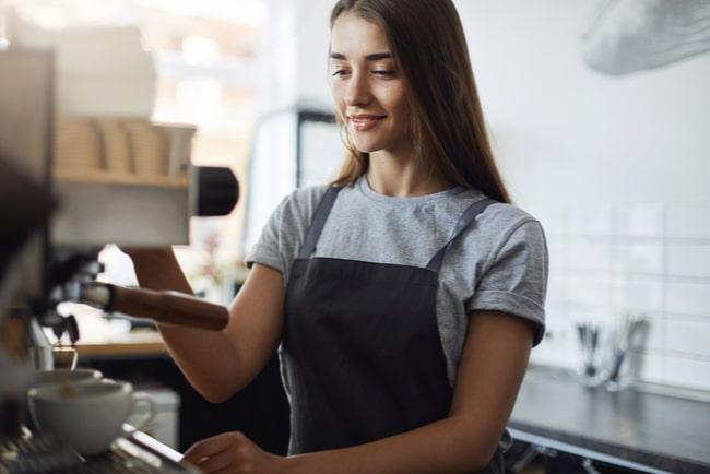 ung kvinna arbetar vid kaffemaskin på café