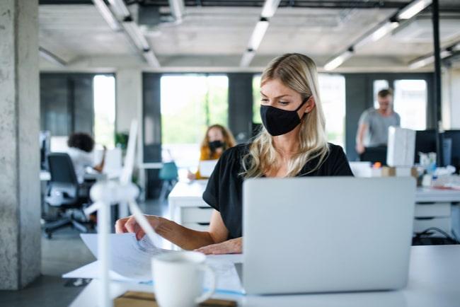 kvinna med munskydd arbetar på kontorsplats med kollegor i bakgrunden
