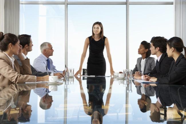 Kvinna står vid huvudänden av ett bord och talar till sina medarbetare som sitter och lyssnar.