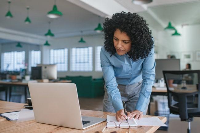 kvinna står lutad över laptop på skrivbord
