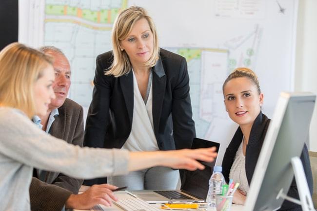 kvinnlig chef lyssnar på medarbetare som pekar på en skärm