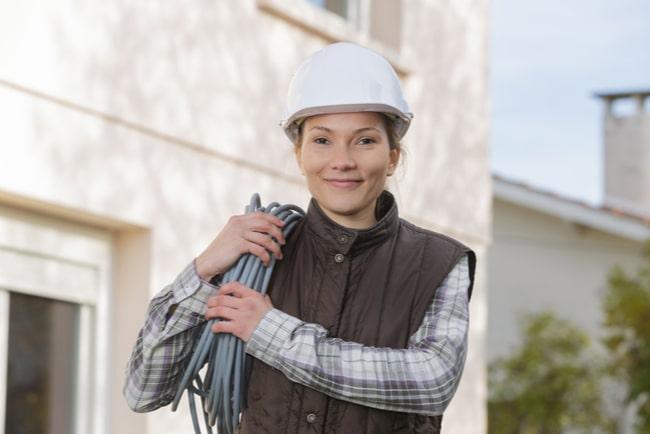 kvinnlig elektriker med elkablar på axeln ler mot kameran
