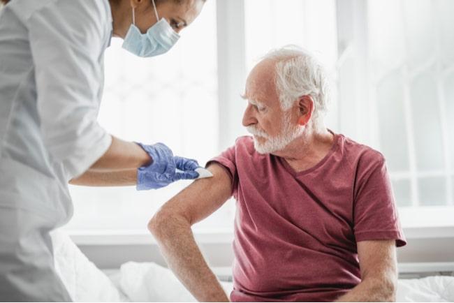 Kvinnlig sjuksköterska ger en äldre man vaccin i hans högra arm.