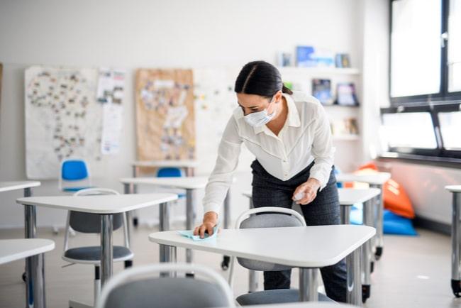 lärare med munskydd spritar av bänkar i klassrum