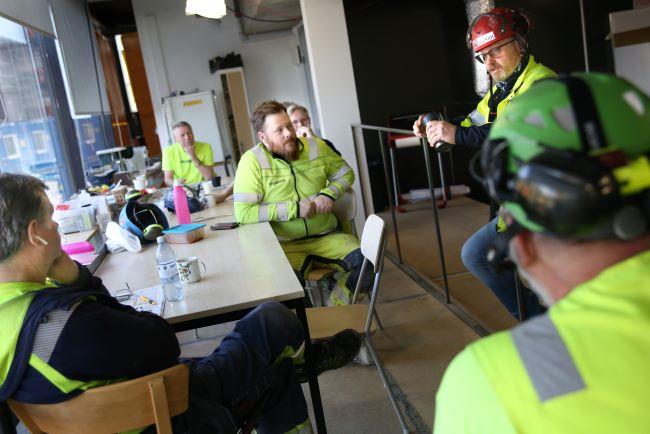 Byggnads ordförande Johan Lindholm pratar med medlemmar på arbetsplats