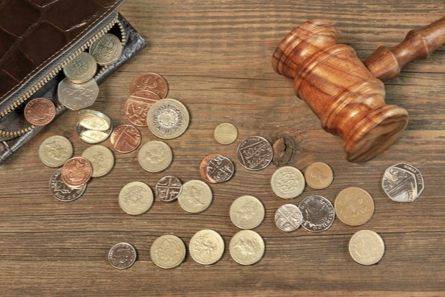 mynt faller ut ur plånbok framför en domarklubba