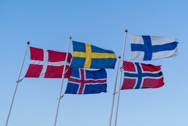 flaggstänger med de nordiska ländernas flaggor mot blå himmel