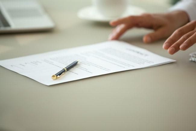 personer skickar över kontrakt och penna över bord