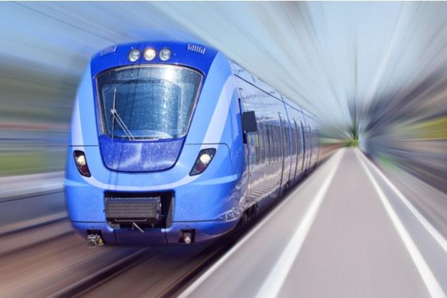 tåg färdas snabb förbi en tågstation mot suddig bakgrund