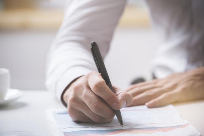 en man signerar avtal
