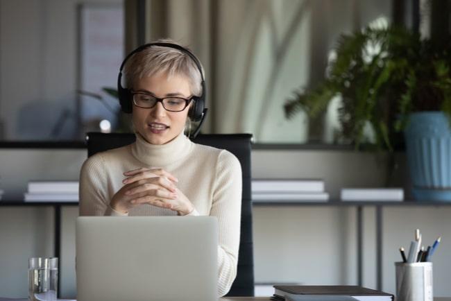 kvinna med hörlurar pratar framför laptop