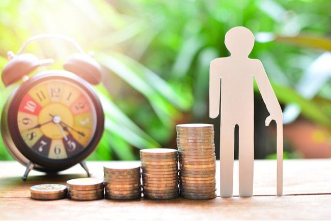 pappersfigur av en äldre man bredvid stegrande högar av mynt och en väckarklocka
