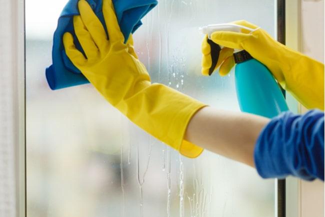 händer i gula handskar putsar ett fönster med blå trasa och sprayflaska