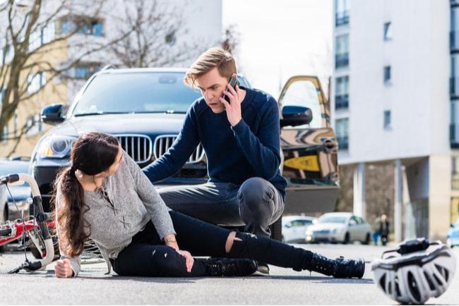 skadad kvinnlig cyklist framför bil