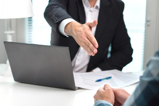 affärsman vid dator sträcker fram handen till en annan person