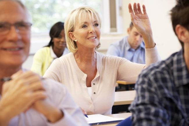 medelålderskvinna i skolklass räcker upp handen