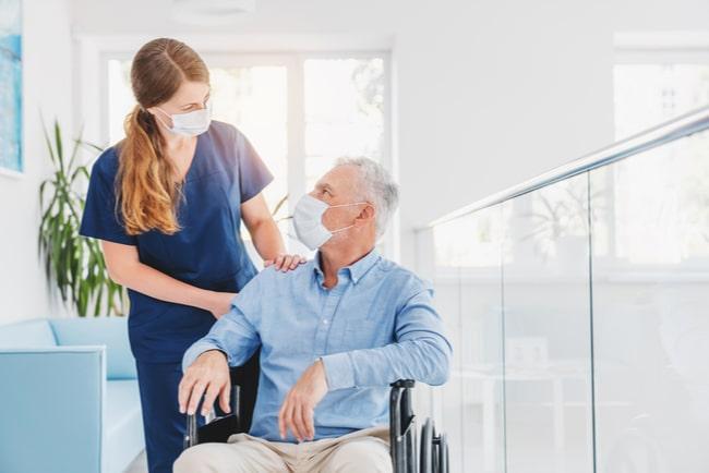 ung undersköterska med munskydd talar med äldre man i rullstol med munskydd