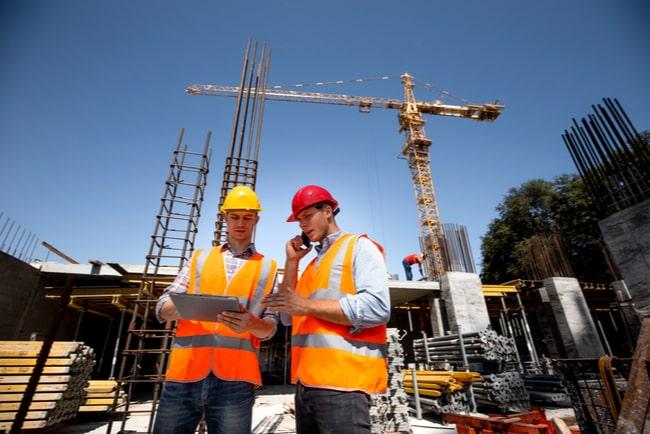 Två män på en byggarbetsplats som står och diskuterar arbetsplatsen.
