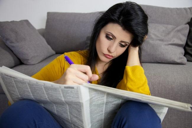 ung uttråkad kvinna letar jobb i en papperstidning