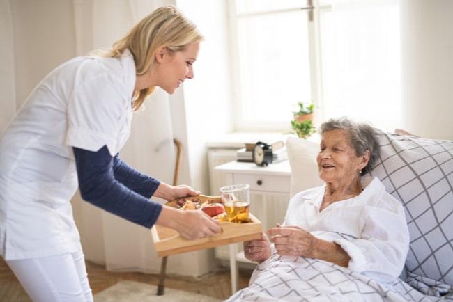 Kvinnlig vårdpersonal kommer med en bricka med mat till en äldre dam som ligger i sin säng.