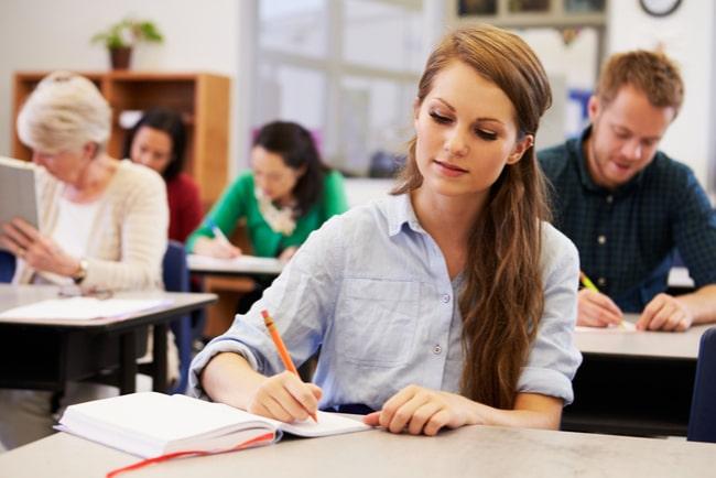 kvinna antecknar i bok i klassrum bland andra vuxna studenter