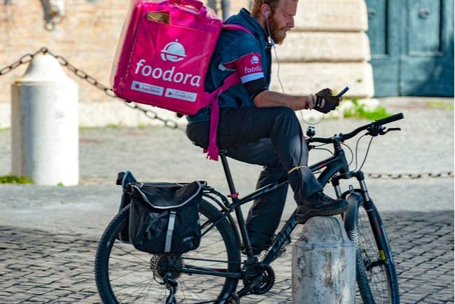 Foodorabud sitter på cykel med mobiltelefon i handen.