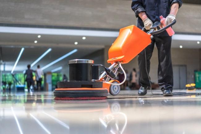 Städare rengör golvet på ett kontor med en skurmaskin.