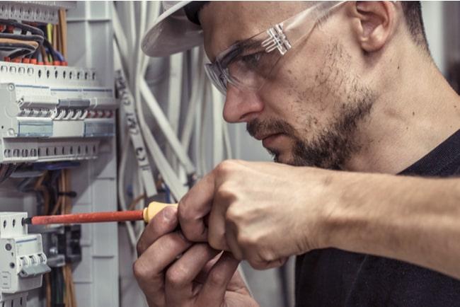 Elektriker arbetar i ett elskåp.